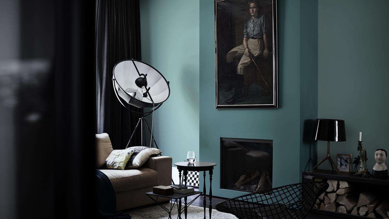 For a bold living room, contrast beautiful lagoon blue walls with furniture in black and charcoal shades.