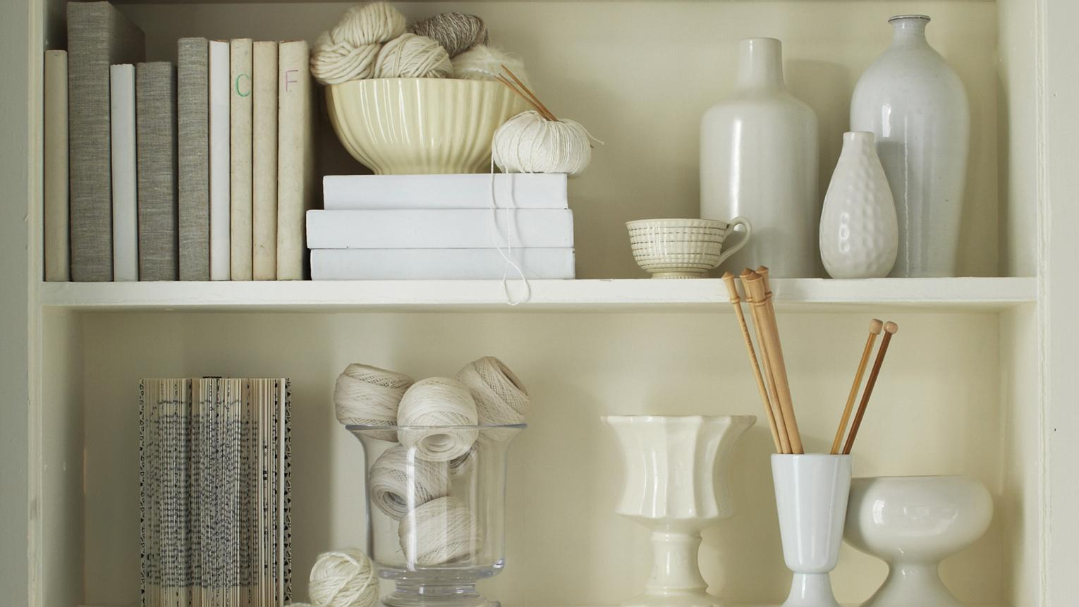 Bookshelves filled with vases, books and precious mementos in beautiful shades of white and off-white.