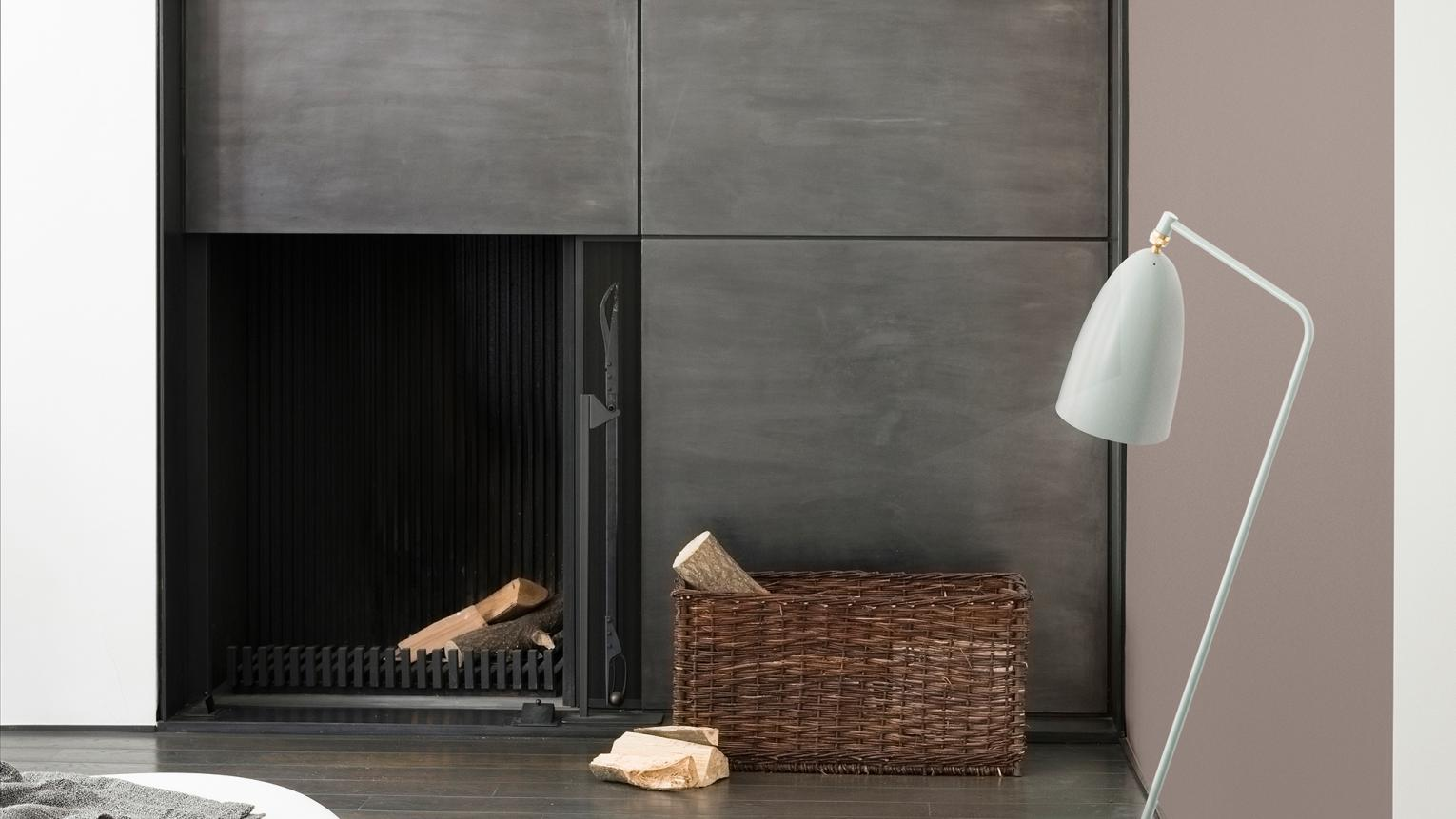 Enhance a minimalist metal fireplace with warm, rich neutrals like dove grey and charcoal.