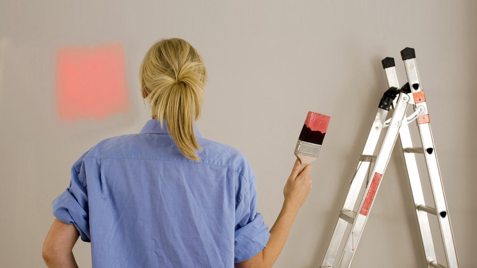 Woman painting her wall with the help of expert decorating tips.